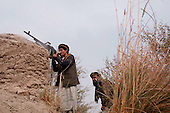 Northern Afghanistan <br /> October 2001<br /> <br /> The Northern Alliance fighter fires a machine gun at the Taliban position 100 meters away at the front line near Khogebha hoddin.