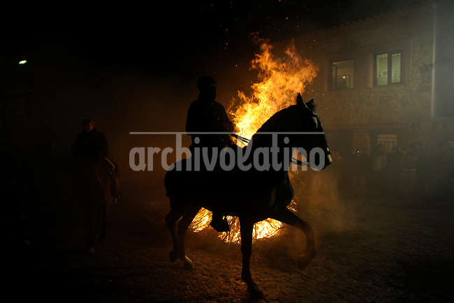 16/1/10. A man rides a horse through a bonfire in San Bartolome de Pinares, 100 kilometers from Madrid, in honor of Saint Anthony, the patron saint of animals. The cermony consist in a religious procession in which horses walk through the smoke produced by the bonfires but many horseriders instead jump with the horse through the bonfires..Photo Ana Laura Castro