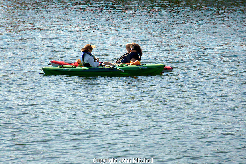 Two women kayakers stopping to chat on False Creek, Vancouver, BC, Canada