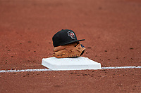A Wisconsin Timber Rattlers hat and glove rests on the field between innings of a Midwest League game against the Lansing Lugnuts at Cooley Law School Stadium on May 1, 2019 in Lansing, Michigan. Wisconsin defeated Lansing 8-3 after the game was suspended from the previous night. (Zachary Lucy/Four Seam Images)
