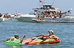 Kevin Strange, foreground right, rows his friends jamie Vogt, left, and Heidi Wilson to shore Memorial Day weekend at the White Trash Bash at Dog Island off the coast of Carrabelle Sunday May 27, 2007.  (Mark Wallheiser/TallahasseeStock.com)