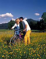 Paar mit Fahrraedern stehen in einer Blumenwiese, kuessen sich | couple with bicycles standing in a flower meadow, kissing