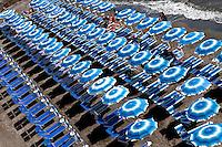 Rows of blue beach umbrellas lined up on beach, Atrani, Amalfi Coast, Italy