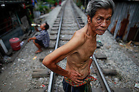 Ded, an elderly Thai man who lives in an impoverished slum in central Bangkok crosses the railway running between shacks February 21, 2011. Data on Monday showed Thailand's economy rebounding from a mild recession in the fourth quarter. The economy, Southeast Asia's second biggest, will feature prominently in a likely general election this year, particularly among the rural and urban poor. In Thailand, the richest 20 percent of the population earn about 55 percent of the income, while the poorest fifth get 4 percent, according to the World Bank.   REUTERS/Damir Sagolj (THAILAND)