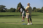 Two African American men playing golf and putting the ball, City Park Golf Course, Denver, Colorao.