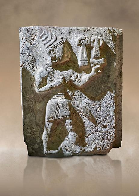 Hittite orthostat relief depicting a god. Hittie Period 1450 - 1200 BC. Hattusa Boğazkale. Hattusa Boğazkale. Çorum Archaeological Museum, Corum, Turkey. Çorum Archaeological Museum, Corum, Turkey. Against a warm art bacground.