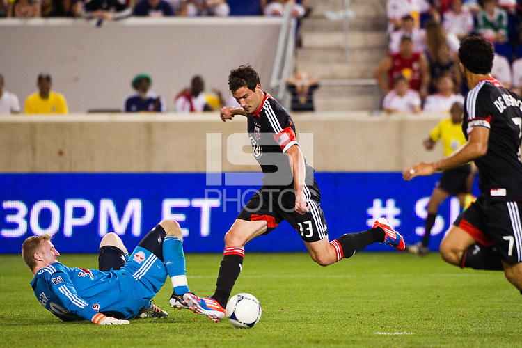 Chris Pontius (13) of DC United shoots and scores on goalkeeper Ryan Meara (18) of the New York Red Bulls. The New York Red Bulls defeated DC United 3-2 during a Major League Soccer (MLS) match at Red Bull Arena in Harrison, NJ, on June 24, 2012.
