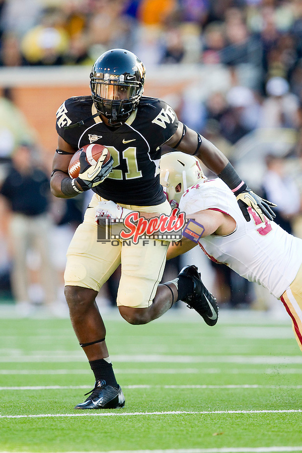 Deandre Martin (21) of the Wake Forest Demon Deacons avoids the tackle attempt by Nick Clancy (54) of the Boston College Eagles during first quarter action at BB&T Field on November 3, 2012 in Winston-Salem, North Carolina.  The Demon Deacons defeated the Eagles 28-14.  (Brian Westerholt/Sports On Film)