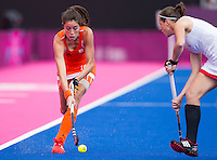 29 JUL 2012 - LONDON, GBR - Naomi van As (NED) of Netherlands (left) makes her way upfield during the women's London 2012 Olympic Games Preliminary round hockey match against Belgium at the Riverbank Arena in the Olympic Park in Stratford, London, Great Britain (PHOTO (C) 2012 NIGEL FARROW)