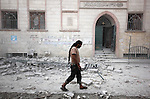 A Syrian man walks on the rubble of buildings after a missile fired by Syrian government forces hit a residential area in the al-Sukari district in the northern Syrian city of Aleppo on September 15, 2015. Photo by Ameer al-Halbi