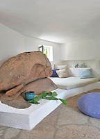 A simple platform bed has been designed around a massive granite boulder which dominates the room