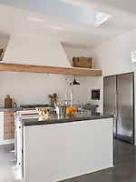The whitewashed rustic kitchen has contemporary worksurfaces of the same polished concrete as the floors