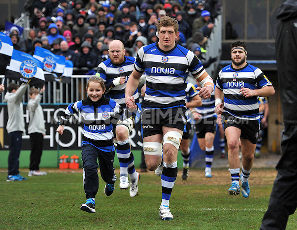 Bath captain Stuart Hooper, mascot in hand, leads the team out onto the field. Aviva Premiership match, between Bath Rugby and Newcastle Falcons on February 8, 2014 at the Recreation Ground in Bath, England. Photo by: Patrick Khachfe / Onside Images