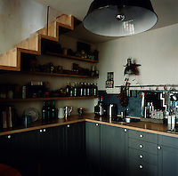 The corner of a compact kitchen with blue/grey painted units and shelving tucked under the open plan staircase