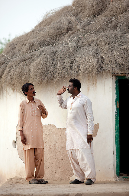 25 JULY 2011: Basti Mahraan Village, Punjab, Pakistan.    Mahar Abdul Latif (R), a former member of Muslim terrorist group Lashkar-i-Taiba (LeT) at his home village of Basti Mahraan in Pakistan with fellow villager Bachu Ram, a Hindu. After Ram offered to donate his rare blood type to save the life of a Muslim woman, relations thawed in the traditional violence between the Muslims and Hindu's of the village. The men are standing outside a Hindu temple that was renovated by the Muslim's of the village in a sign of solidarity.Picture by Graham Crouch/Toronto Star