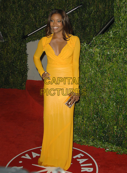 GABRIELLE UNION.The 2010 Vanity Fair Oscar Party held at The Sunset Tower Hotel in West Hollywood, California, USA..March 7th, 2010.oscars full length yellow long sleeves gold clutch bag dress hand on hip.CAP/RKE/DVS.©DVS/RockinExposures/Capital Pictures.