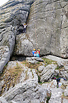 Children rock climbing on the granite tor of Haytor, Dartmoor national park, Devon, England, UK