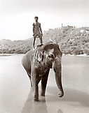 INDIA, Jaipur, man on elephants back in river in front of the Amber Palace (B&W)