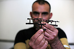 "Palestinian artist Majdi Abu Takeya, 39, converts gunshots used by the Israeli security forces against Palestinian protesters to small pieces of art knows as ""Art of thumbnails"" at his house in Nuseirat in the central Gaza Strip, on February 16, 2019. Photo by Dawoud Abo Alkas"