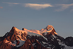 Golden frst light at sunrise on Cerro Paine Grande.  At left is Bariloche Point, then the Central Summit and the Main Summit at far right.  Torres del Paine National Park in Patagonia, Chile.  A UNESCO World Biosphere Reserve.