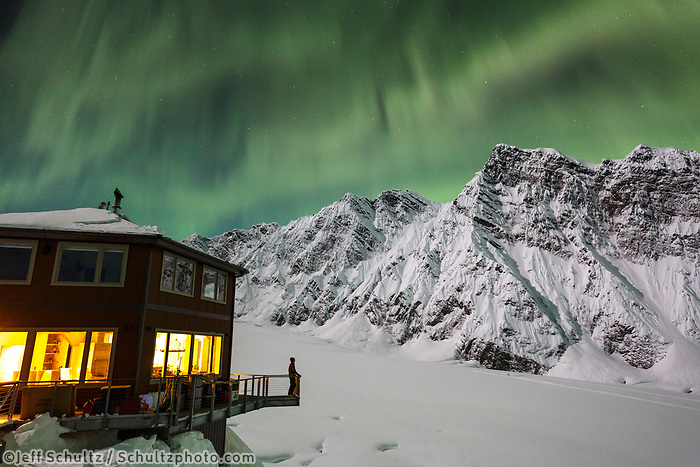 A guest views the Aurora Borealis (Northern Lights) from the observation deck of the Sheldon Chalet in the Alaska Range in the Don Sheldon Amphitheater.  Ruth Glacier