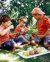 A group of three young boys eating muffins in dappled sunlight in the garden