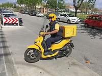Spanish postman on a yellow scooter delivers mail in San Pedro de Alcantara, Malaga Province, Spain, 18th March 2019, 201903181217<br /><br />Copyright Image from Victor Patterson, 54 Dorchester Park, <br />Belfast, UK, BT9 6RJ<br /><br />t1: +44 28 9066 1296 (from Rep of Ireland 048 9066 1296)<br />m: +44 7802 353836<br />e: victorpattersonbelfast@gmail.com<br />w: www,victorpatterson.com<br /><br />Please see my Terms and Conditions of Use at https://www.victorpatterson.com/page2<br />It is IMPORTANT that you familiarise yourself with them.<br /><br />Images used on the Internet incur an additional cost and must be visibly watermarked i.e. © Victor Patterson within the body of the image and copyright metadata must not be deleted. Images used on the Internet have a size restriction of 4kbs and are chargeable at rates available at victorpatterson.com.<br /><br />This image is only available for the use of the download recipient i.e. television station, newspaper, magazine, book publisher, etc, and must not be passed on to any third party. It is also downloaded on condition that each and every usage is notified within 7 days to victorpattersonbelfast@gmail.com.<br /><br />The right of Victor Patterson to be identified as the author is asserted in accordance with The Copyright Designs And Patents Act (1988). All moral rights are asserted.