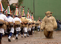 ITUREN, NAVARRE - JANUARY 30: A group of 'Zanpantzar', people dressed in sheep fur and big cowbells tied to their back, and the 'Artza' (Bear) (R) march across Ituren village during an ancient traditional carnival on January 30, 2006. Zanpantzar´s march trough Ituren farmhouses and streets sounding their cowbells to wake up the earth for a good new farmer year and keep far away all bad spirits . Photo by Ander Gillenea