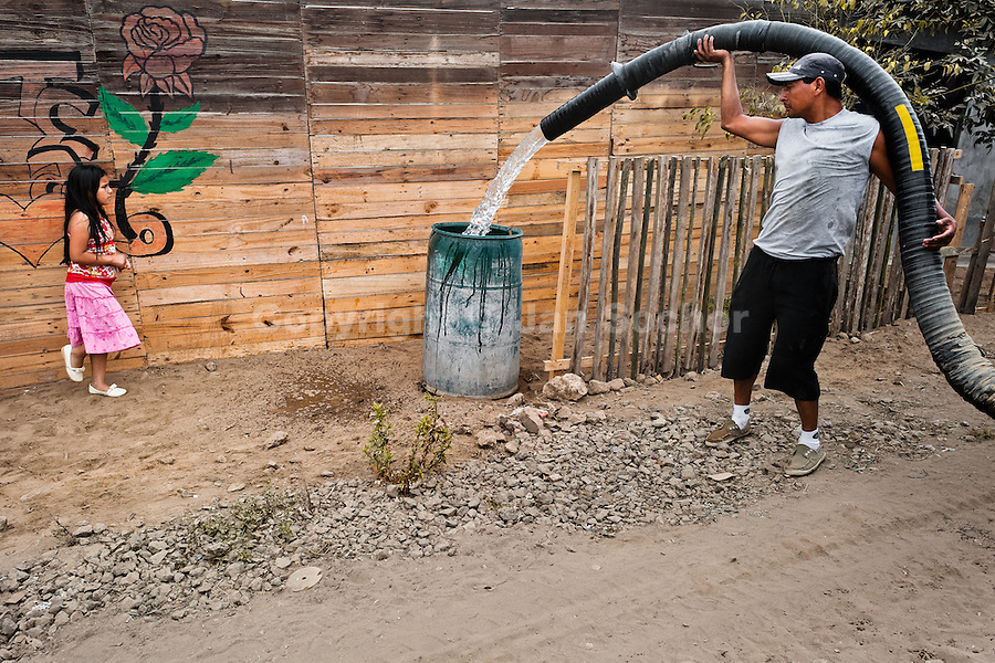 A Peruvian water distribution worker with a pipe splashes drinking water into a plastic barrel on the dusty hillside of Pachacútec, a desert suburb of Lima, Peru, 21 January 2015. Although Latin America (as a whole) is blessed with an abundance of fresh water, having 20% of global water resources in the the Amazon Basin and the highest annual rainfall of any region in the world, an estimated 50-70 million Latin Americans (one-tenth of the continent's population) lack access to safe water and 100 million people have no access to any safe sanitation. Complicated geographical conditions (mainly on the Pacific coast), unregulated industrialization (causing environmental pollution) and massive urban poverty, combined with deep social inequality, have caused a severe water supply shortage in many Latin American regions.