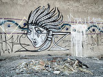 Indian-alien graffiti on side of old transformer building, Alkali, Nev.