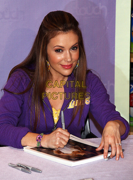 "ALYSSA MILANO.Showcases Her ""Touch"" NBA line of Women's Apparel held at the NBA Store Fifth Avenue New York City, USA,.15th April 2009..half length purple LA Lakers top jacket spot sports sitting signing .CAP/ADM/PZ.©Paul Zimmerman/Admedia/Capital Pictures"