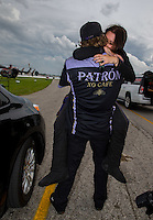 Sept. 1, 2014; Clermont, IN, USA; NHRA funny car driver Alexis DeJoria celebrates in the arms of husband Jesse James after winning the US Nationals at Lucas Oil Raceway. Mandatory Credit: Mark J. Rebilas-USA TODAY Sports