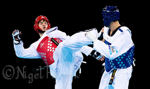 04 DEC 2011 - LONDON, GBR - Aaron Cook (GBR) (on left, in red) tries to strike Nicolas Garcia (ESP) (on right, in blue) during their men's -80kg category semi final contest at the London International Taekwondo Invitational and 2012 Olympic Games test event at the ExCel Exhibition Centre in London, Great Britain .(PHOTO (C) NIGEL FARROW)