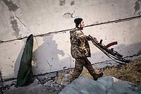 """UKRAINE, 03.2015, Peski. In dem umkaempften Dorf unweit des Donezker Flughafens laeuft ein Soldat des """"Rechter Sektor"""" Freiwilligenbataillons.   In the frontline village close to the Donetsk airport a soldier of the """"Right Sector"""" volunteer battalion is seen.  © Arturas Morozovas/EST&OST"""