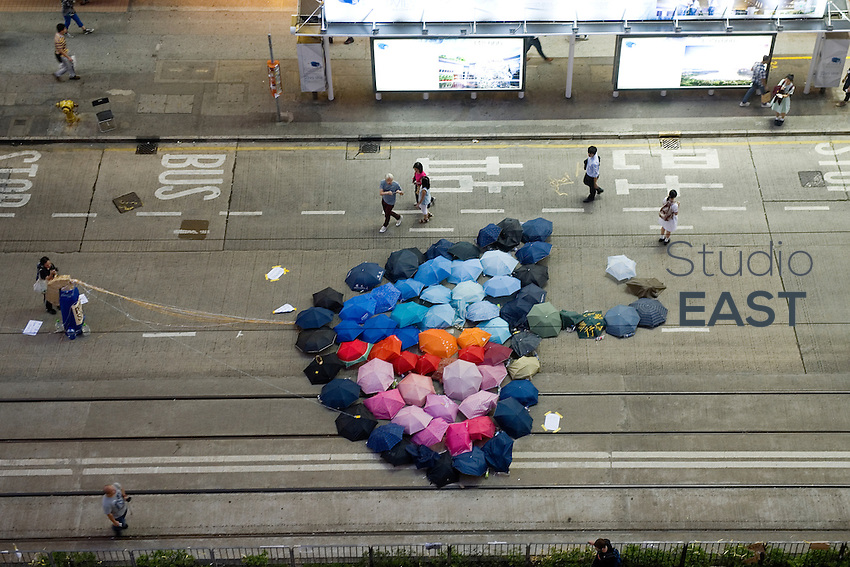 HONG KONG, HONG KONG SAR, CHINA - OCTOBER 13: A giant umbrella made of umbrellas adorn the pavement in the 'Occupy Central' camp of Causeway Bay, Hong Kong, China, on October 13, 2014. The 'Umbrella revolution' or 'Occupy Central' is a civil disobedience movement that began in response to China's decision to allow only Beijing-vetted candidates to stand in the city's 2017 election for the top civil position of chief executive. Thousands of pro-democracy supporters are calling for open elections and the resignation of Hong Kong's Chief Executive Leung Chun-ying. (Photo by Lucas Schifres/Getty Images)