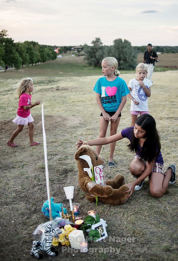 Desiree Figueroa (cq),11 places a bear at a shrine during a vigil is held next the Aurora Century 16 movie theater where James Holmes (cq), 24, is in custody and is suspected of killing 12 people and wounding many more in Aurora, Colorado, Friday, July 20, 2012. The shootings occurred during the midnight premiere of the new Dark Knight Batman movie...Photo by MATT NAGER