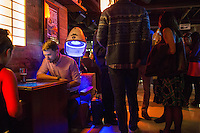 Emily Benotti (left) and Jason Lowell play a free Ms. Pac-Man machine at Hojoko, a Japanese bar and restaurant in The Verb Hotel in the Fenway neighborhood of Boston, Massachusetts, USA, on Friday, Dec. 4, 2015.