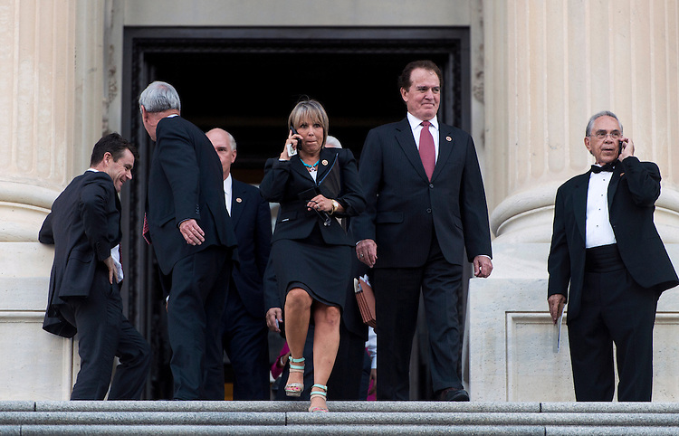 UNITED STATES - SEPTEMBER 18: From left, Rep. Michelle Lujan Grisham, D-N.M., and Rep. Phil Gingrey, R-Ga., walk down the House steps as the tuxedo-clad Rep. Ruben Hinojosa, D-Texas, talks on his cell phone on Thursday, Sept. 18, 2014, following the final vote in the House of Representative before the mid-term elections. (Photo By Bill Clark/CQ Roll Call)