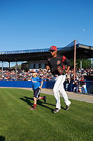 Batavia Muckdogs right fielder Jhonny Santos (13) takes the field with a young fan during introductions before a game against the Auburn Doubledays on July 4, 2017 at Dwyer Stadium in Batavia, New York.  Batavia defeated Auburn 3-2.  (Mike Janes/Four Seam Images)