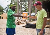 NWA Democrat-Gazette/CHARLIE KAIJO (From left) Asee Mason of Eureka fistbumps Dr. Dan Bell, Friday, June 8, 2018 on Passion Play Road, across the street from the Washington Regional clinic in Eureka Springs. <br /><br />Eight tiny houses are being built in Eureka Springs, which has a dearth of affordable housing. They're being constructed by 66 volunteers from 13 states with World Mission Builders. They began work on Monday (June 4) and should finish most of the construction by the end of next week (June 15). Then local volunteers will finish out the interiors and put shingles on the roofs. The first eight houses are part of what will be called ECHO Village. Plans are to eventually have 26 houses in the village. It's a project of Eureka Christian Health Outreach, which bought 10 acres for the village. The same group started ECHO Clinic in Eureka Springs in 2005. It provides free medical care to the uninsured and people on a low income.