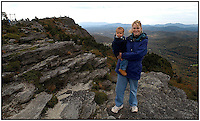 A mother holds her son at the tallest point of Grandfather Mountain, in Avery County, NC. Grandfather Mountain is a popular mountain and state park located near Linville, North Carolina. It is the highest peak in the eastern escarpment of the Blue Ridge Mountains. Mother and son are model released.