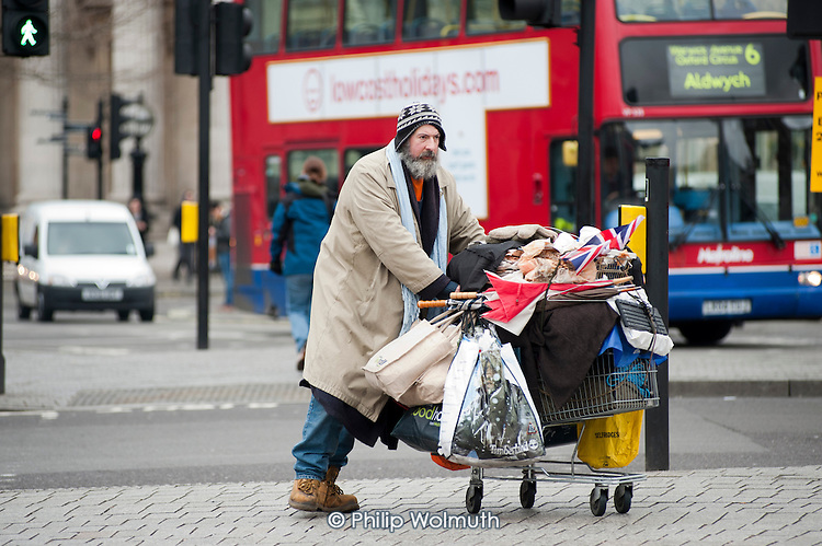 A man pushes his possessions in a shopping trolley in Trafalgar Square.
