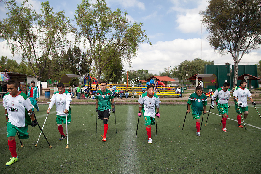 "Players from Guerreros Aztecas warm up by running lengths of the pitch, before a soccer game against Los Dragones (""the Dragons"")  in Deportivo Tlalli II in Talnepantla, Mexico on September 27, 2014. Guerreros Aztecas (""Aztec Warriors"") is Mexico City's first amputee football team. Founded in July 2013 by five volunteers, they now have 23 players, seven of them have made the national team's shortlist to represent Mexico at this year's Amputee Soccer World Cup in Sinaloa this December. The team trains twice a week for weekend games with other teams. No prostheses are used, so field players missing a lower extremity can only play using crutches. Those missing an upper extremity play as goalkeepers. The teams play six per side with unlimited substitutions. Each half lasts 25 minutes. The causes of the amputations range from accidents to medical interventions – none of which have stopped the Guerreros Aztecas from continuing to play. The players' age, backgrounds and professions cover the full sweep of Mexican society, and they are united by the will to keep their heads held high in a country where discrimination against the disabled remains widespread. (Photo by Bénédicte Desrus)"