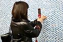 "A woman takes a photograph of a wall of 100,000 Slime characters in Shinjuku Station on February 26, 2015. 100,000 Blue Slime from the game of Dragon Quest are displayed in bubble-wrap in a corridor of Shinjuku Station. The wall was created to promote the newest video game ""Dragon Quest Heroes: The Dark Dragon and the World Tree Castle"" for Playstation 3 and 4. Passersby can pop the Slimes and the goal of for all 100,000 bubbles to have been burst by the end of the campaign. There are special characters such as metal Slimes and Rockbombs hidden along the wall and the installation is accompanied by background music from the game. The promotion runs from February 23rd to March 1st in Tokyo. (Photo by Rodrigo Reyes Marin/AFLO)"