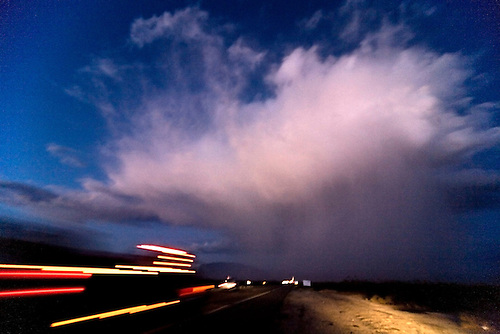 VEHICLES ON INTERSTATE 15 IN THE MOJAVE DESERT OF CALIFORNIA DRIVE INTO AN EVENING RAIN STORM.