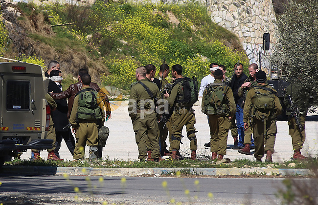 Israeli security forces arrest a Palestinian police officer, at the Israeli checkpoint of Beit El settlement, near the West Bank city of Ramallah, March 5, 2015. Photo by Shadi Hatem