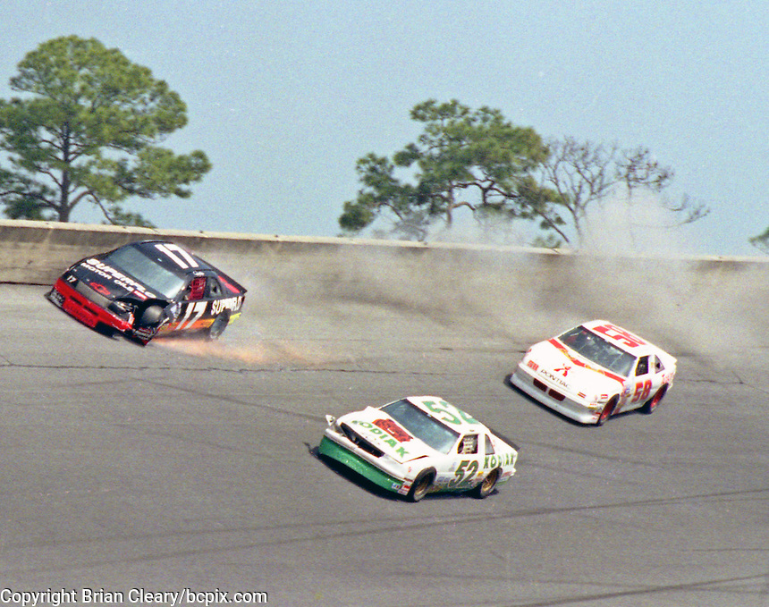 iThe cars of Darrell Waltrip (17), Ken Schrader (52),  and Ernie Irvan (58) are among the cars involved in one of the biggest crashes in the history of Daytona Internationa Speedway , a 24 car accident during the Goody's 300, NASCAR Busch Series, Daytona Beach, FL, February 17, 1990.  (Photo by Brian Cleary/www.bcpix.com)
