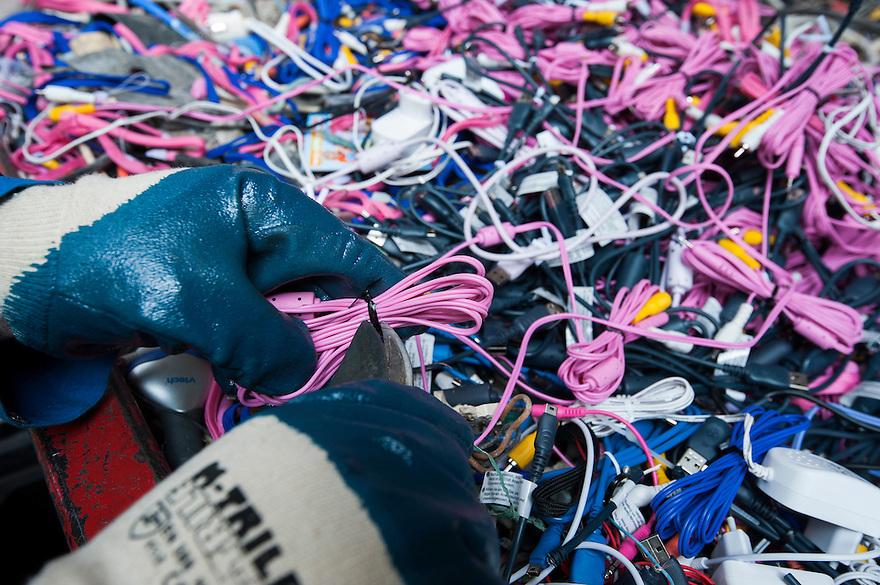 Nederland, Amsterdam, 29 aug 2013<br /> Afvalscheiding bij Afval Energie Bedrijf Amsterdam.<br /> Werkervaringsproject van Milieuwerk EcoCollege.<br /> Kabeltjes worden ontdaan van stekkertjes. <br /> Foto(c): Michiel Wijnbergh