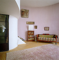 An Empire sofa occupies a wall of the pink living room