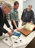David Creech, David Sawyer and John Green examine some of the St. John's Masonic Lodge artifacts that are on loan to the History Center.  Chuck Beckley/ The Sun Journal